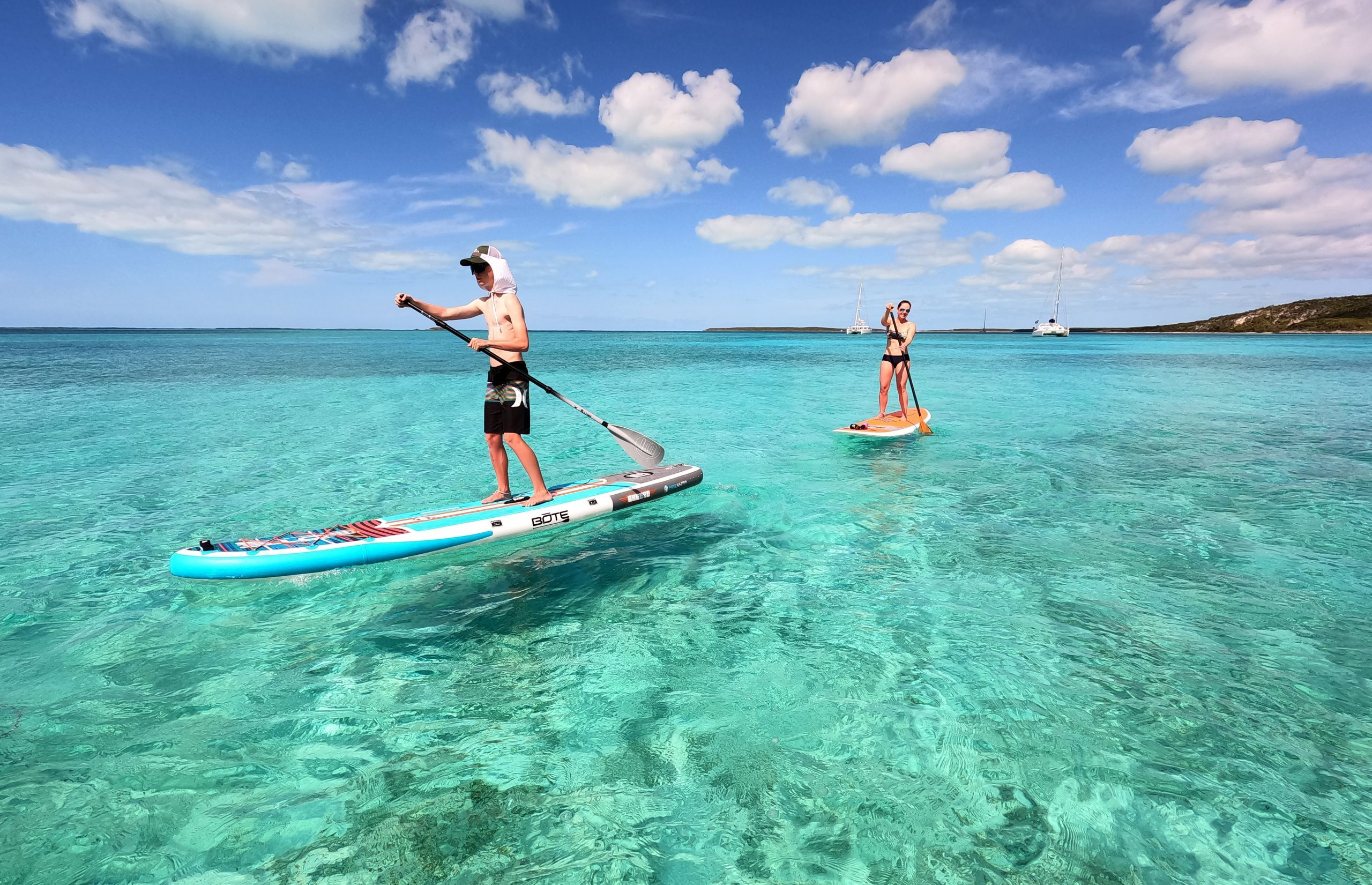 A teenager and his mother paddleboard in clear Bahamian waters