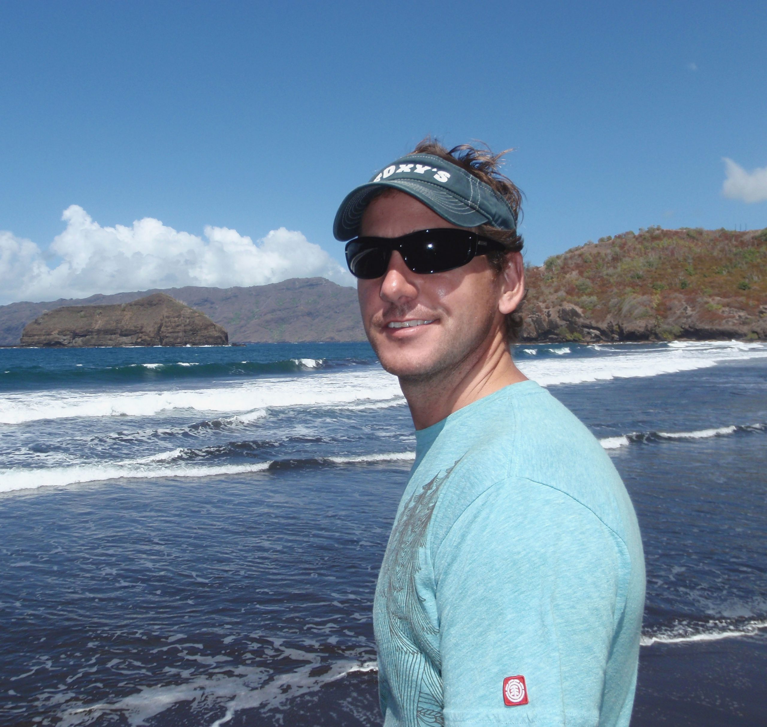 Photo of man with sunglassses in front of waves on a beach in French Polynesia