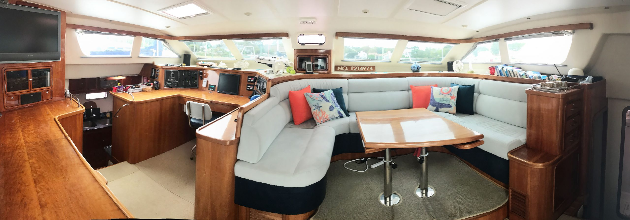 Salon with large sofa, dining table and nav station