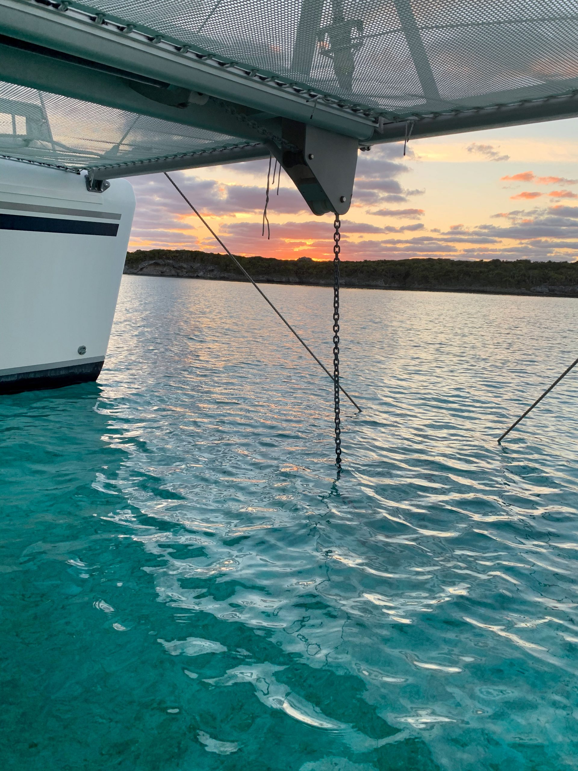 Sunset viewed from beneath the trampolines on a catamaran